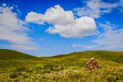 Rolling Hills lisse avec une pile des roches rouges vers la droite, ciel bleu lumineux à l'Inner Mongolia Chine photos libres de droits