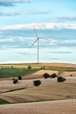 Rolling hills with a single wind turbine. Rolling agricultural hills with a single wind turbine in the distance on the horizon providing renewable electricity Royalty Free Stock Photos