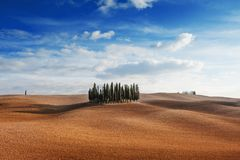 Rolling hills, small cypress trees forest and blue sky with clouds in tuscan landscape countryside panoramic view in an autumn day. Tuscany, Italy, Europe Royalty Free Stock Photography