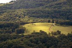 Rolling hills of west virginia. A view of green rolling hills and a farm atop a hill in lost river state park in West Virginia Stock Photography