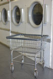 Washday Rolling Laundry Basket With Dryers. Rolling laudry basket with dryers at local laudromat Stock Images