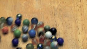 Rolling marbles on wooden board stock video footage