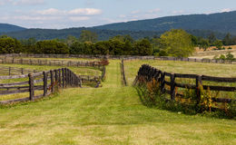 Rolling meadows with wooden fences and hills Stock Photo