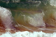Rolling multi layered wave breaking on sand royalty free stock images