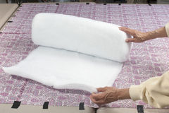 Rolling out batting. Preparing to unroll polyester batting for use in a quilt Royalty Free Stock Image