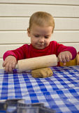 Rolling out the dough. Toddler (2 years old) rolling out dough for gingerbread cookies Stock Photo