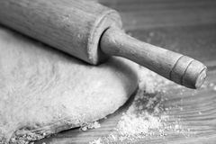 Rolling out the dough in black and white. Black and white image of rolling pin and dough Royalty Free Stock Photos