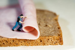 Rolling Out The Ham. Macro of tiny miniature figure of a workman rolling out a slice of ham Stock Photos