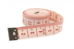 Rolling out measuring tape, on its side. Rolling out a measuring tape, isolated on white background. Rolled up on it's side Stock Photography