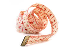 Rolling out measuring tape, on its side. Rolling out a measuring tape, isolated on white background. Rolled up on it's side. Unravelled royalty free stock image