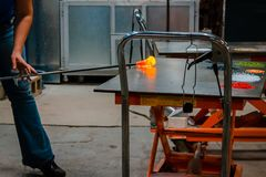 Rolling out molten glass to blow into a bowl Royalty Free Stock Photo