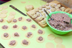 Rolling pin, dough and raw pelmeni Stock Photography