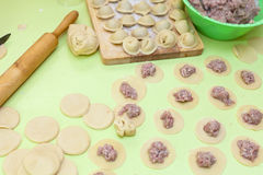 Rolling pin, dough and raw pelmeni Royalty Free Stock Image