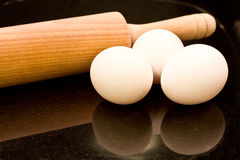 Rolling pin, eggs. On black background Stock Image