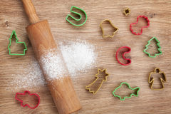 Rolling pin with flour and cookie cutters on wooden table Stock Image