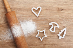 Rolling pin with flour and cookie cutters on wooden table Royalty Free Stock Photo