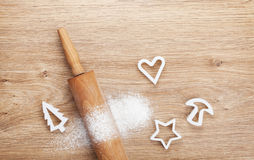 Rolling pin with flour and cookie cutters on wooden table Stock Images