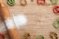 Rolling pin with flour and cookie cutters on wooden table Royalty Free Stock Image