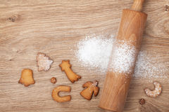 Rolling pin with flour and cookies on wooden table Royalty Free Stock Photo