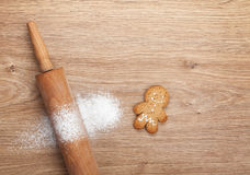 Rolling pin with flour and gingerbread cookie on wooden table Stock Images