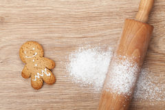 Rolling pin with flour and gingerbread cookie on wooden table Royalty Free Stock Photos