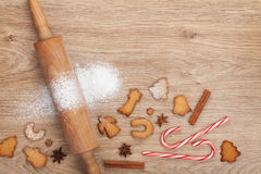 Rolling pin with flour, spices and cookies on wooden table Stock Photo