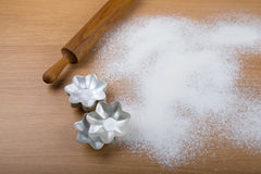 Rolling pin, forms for baking and flour sprinkled on a light woo Stock Images