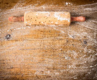 Rolling pin on old wooden background with  wheat flour, top view Royalty Free Stock Photography