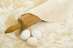 Rolling-pin, pastry and eggs Stock Photo