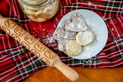 Rolling pin with a pattern on a wooden decorated table covered with baked flour. Rolled dough with a pattern and cookie of various stock image