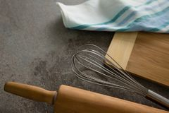 Rolling pin, whisker, chopping board and cloth on table. Close-up of rolling pin, whisker, chopping board and cloth on table royalty free stock images
