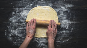 Rolling pizza dough. Female hands rolling dough for pizza on a dark wooden table Royalty Free Stock Photos