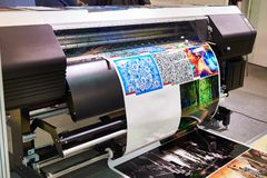 Rolling plotter printer in work. Big rolling wide plotter printer in work stock photo