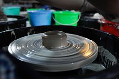 Rolling pottery machine in China. Hand made pottery cup still in a rolling plate in a light Royalty Free Stock Photo
