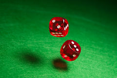 Rolling red dice. Over green surface Stock Photos