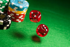 Rolling red dice on a casino table. With chips Stock Photo