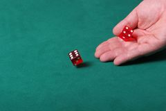 Rolling rolling rolling. Dices being thrown in a craps game, or yatzee or any kind of dice involved game, Dices are a clear red color on a green felt table Stock Photo