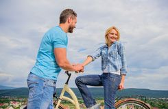 Rolling romance or bike date. Man with beard and shy blonde girl on first date. Woman feels shy in company with royalty free stock images