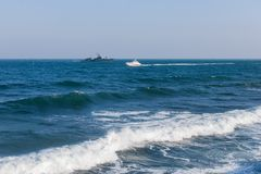 Seascape with military ship and motor yacht Stock Images