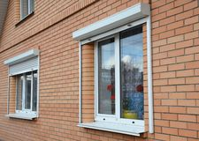 Rolling shutters house windows protection. Brick house with metal roller shutters on the windows stock images