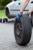 Rolling a spare of wheel Royalty Free Stock Photo