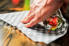 Rolling a sushi burrito with checkered paper. Chef is rolling a sushi burrito in a checkered style take out paper Stock Photo