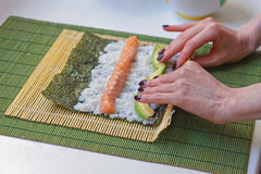 Rolling sushi. Woman rolling sushi with bamboo mat Stock Photos