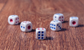 Rolling three dice on a wooden desk.  Stock Photography