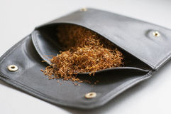 Rolling tobacco in a leather black pouch Royalty Free Stock Images