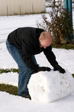 Rolling up the Snow. A Man rolling up the snow in his backyard Stock Image