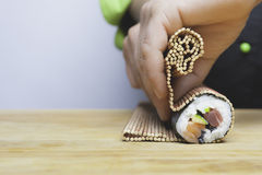 Rolling up sushi. Closeup of chef hands rolling up sushi on a bamboo mat Stock Photography