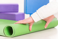 Rolling up a yoga mat. On the floor Stock Photography