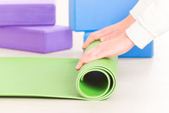 Rolling up a yoga mat Royalty Free Stock Photo