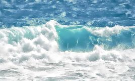 The rolling wave picks up the light and glows a beautial aqua-blue. Waves splash the beachfront all day with a stunning array of colors and raw power stock photo
